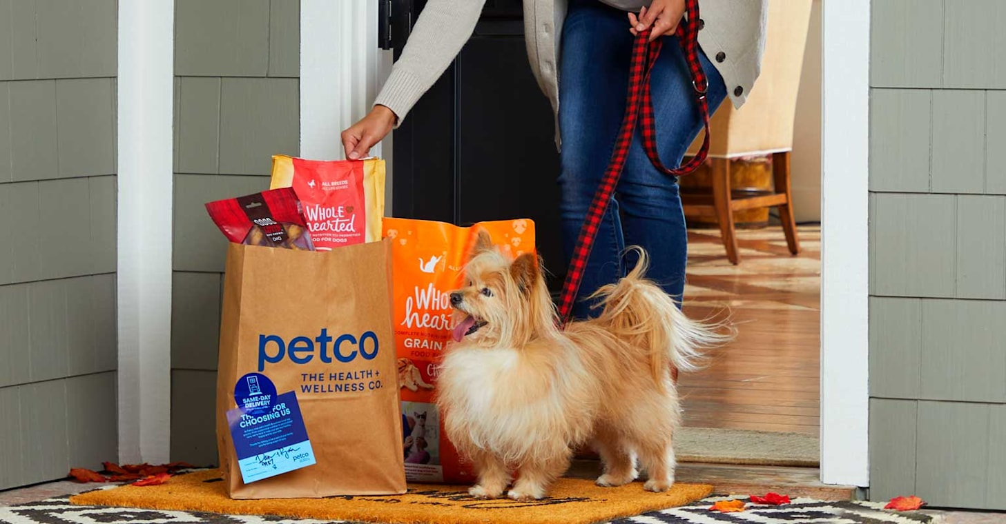 Woman and Terrier answer door to receive a Petco order.