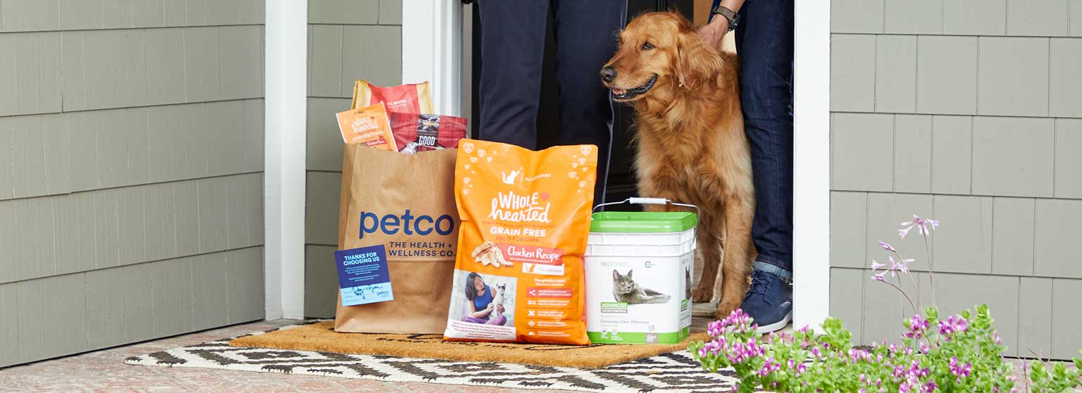 Two men with a cat and a dog answering the door to receive a Petco order.